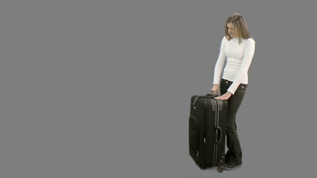 Woman with suitcase waits for her companion