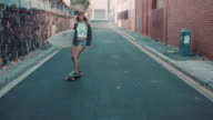 Woman with surfboard skating on street