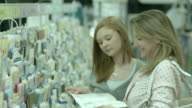 MS, TU, SELECTIVE FOCUS, Woman with teenage daughter (16-17) choosing greeting card in pharmacy aisle, Scotch Plains, New Jersey, USA