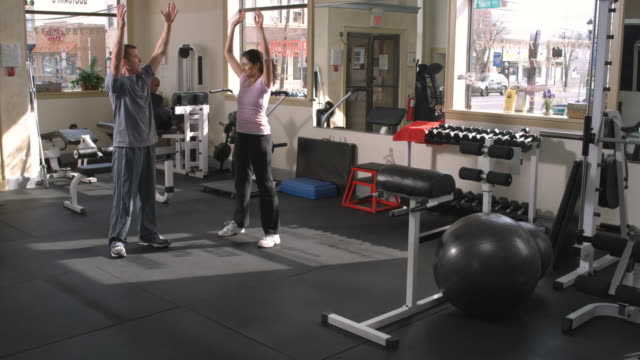 WS, Woman with trainer exercising in gym, Garwood, New Jersey, USA