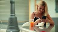 Donna che lavora al bar con telefono cellulare