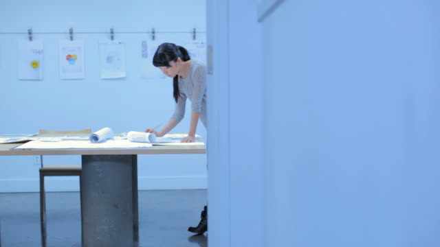 WS PAN Woman working on blueprint in architecture firm / Vancouver, BC, Canada