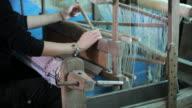 Woman working on weaving loom