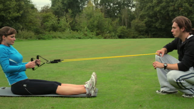 MS Woman working out with resistance bands with personal trainer in park, London, England