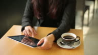 Woman working with Digital Tablet in a Cafe, Close up