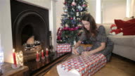 Woman wrapping a large Christmas present