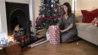Woman wrapping Christmas Presents by the tree