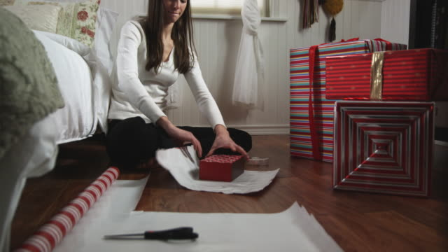 woman wrapping presents in her bedroom