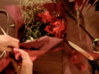 CU HA Woman wrapping satin ribbon around bouquet of roses, New Zealand