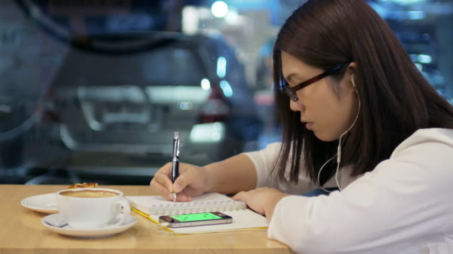 Woman writing in notebook at coffee cafe with coffee , cake and smartphone , 4k(UHD)