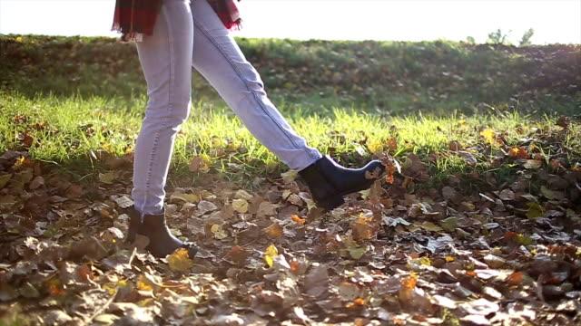 Dames voeten lopen door gedroogde bladeren
