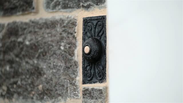 Woman's finger rings doorbell (ECU)