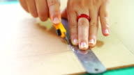 Woman's hand cutting pattern on acrylic sheet with Plastic Cutting Tools.