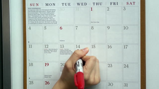 CU Woman's hand drawing heart on Valentine's Day on wall calendar, Scarborough, New York, USA