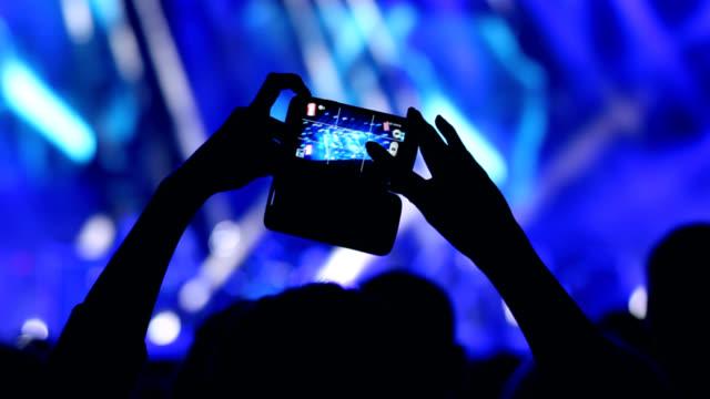Donna mano tiene un telefono intelligente durante un concerto