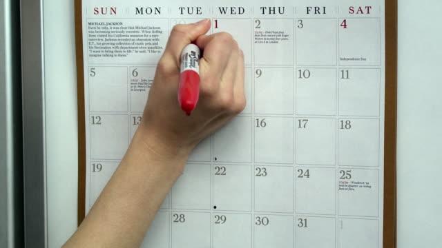 CU Woman's hand marking diet days on wall calendar, Scarborough, New York, USA