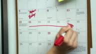 CU Woman's hand marking springs break on wall calendar, Scarborough, New York, USA