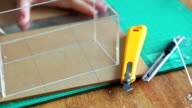 Woman's hand measuring ruler master skin for acrylic sheet and cutting pattern on acrylic sheet with Plastic Cutting Tools.