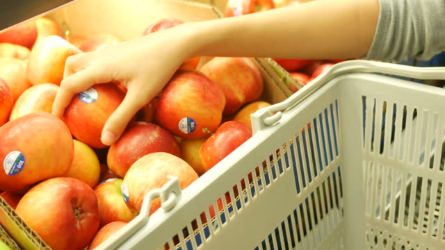 Woman's hand shopping in supermarket , select apple