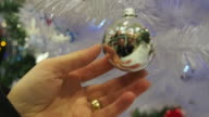 Woman´s hand touching a Christmas ball in a white artificial christmas tree.
