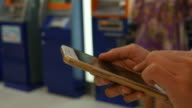 Woman's hand using smart phone in bank