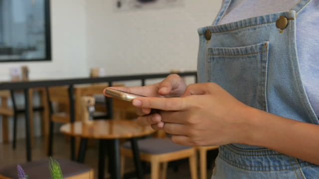Woman's hand using smart phone in coffee shop