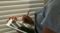 woman's hand using tablet near window