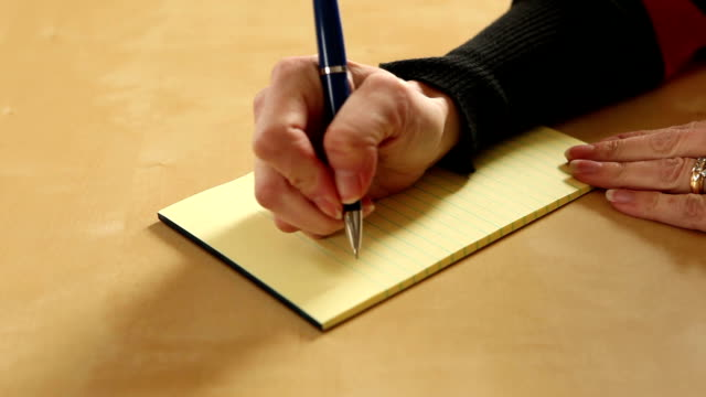 Woman's Hand Writing 'To Do' List