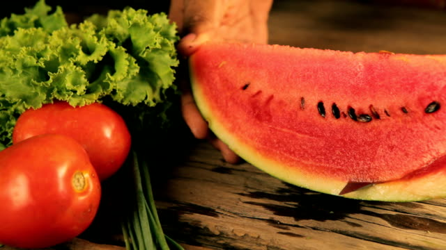 Woman's hands cutting watermelon, behind fresh vegetables