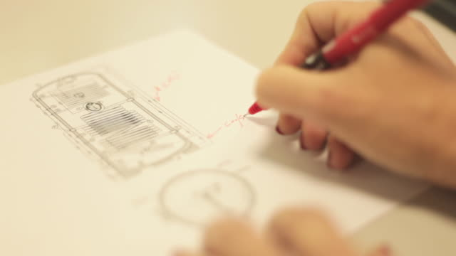 Womans hands making red corrections in document