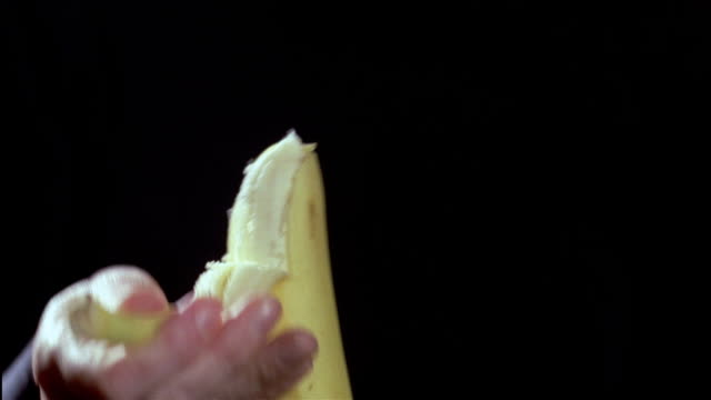 CLOSE UP woman's hands peel a banana.