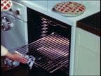 1946 woman's hands putting 2 pies onto oven rack + pushing rack into oven + closing oven door