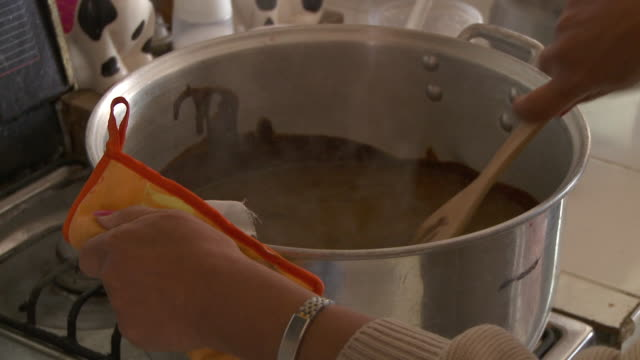 CU Woman's hands stirring pot of mole sauce / Cuernavaca, Morelos, Mexico