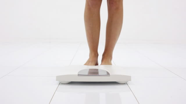 Woman's legs on the white scale.