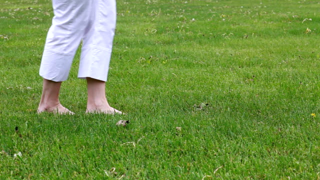 Woman's legs stepping on grass