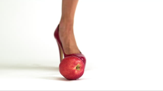 CU SLOW MO Woman's red heel crushes and smashes a red apple on white background