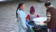 Women and child setting up food cart, Cochabamba, Bolivia