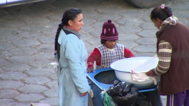 Women and child setting up food cart, Cochabamba, Bolivia