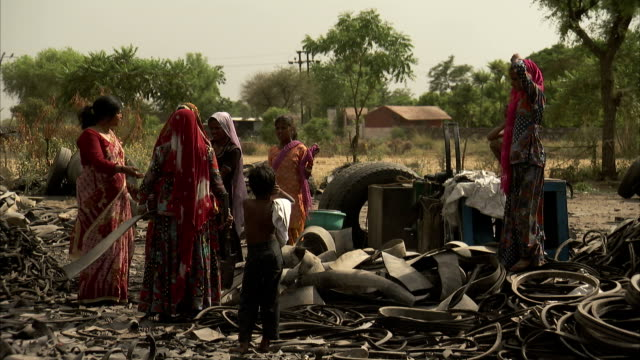 Women and children surrounded by old tyres and scrap.