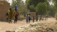WS, Women and children walking on dirt road in village, near Niono, Mali