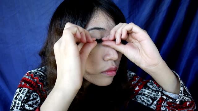 Women are applying the false eyelashes