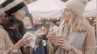 Women are eating street food at outdoor food market.