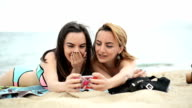 Women at the beach taking selfies.