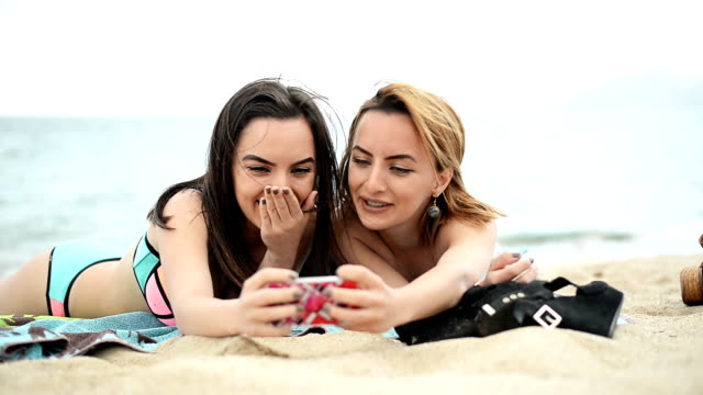 Women at the beach taking selfies.