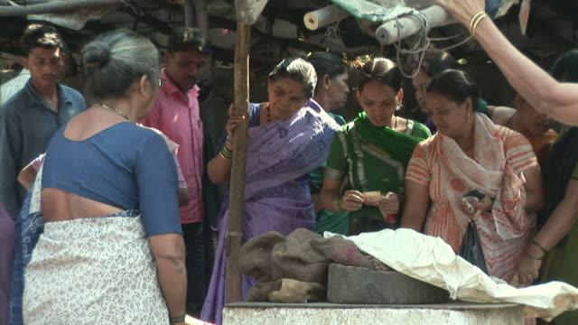 MS Women buying food at street market / Dharavi Mumbai India