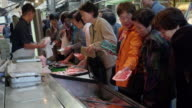 Women buying fresh seafood at Tsukiji Market
