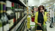 Women buying wine in supermarket