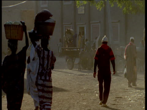 Women carry baskets on their heads through Djenne's dusty streets