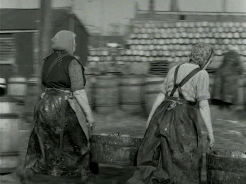 Women carry buckets of fresh herring to be processed at Great Yarmouth