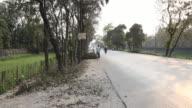 Women carrying huge sacks on their heads on road near tea plantation near Siliguri, India